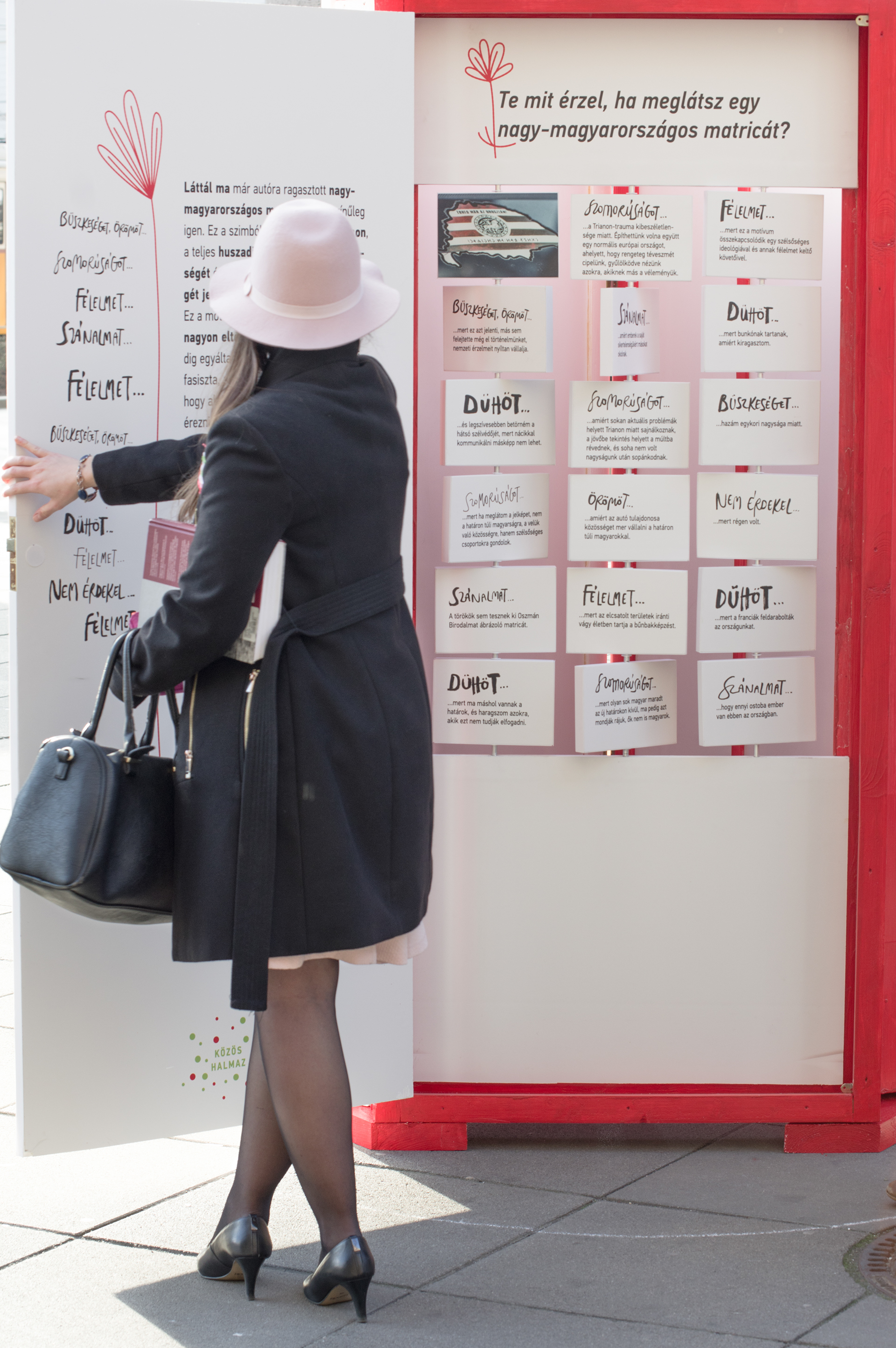 woman in pink hat standing in front of a door with handwriting and illustrations that's part of the exhibition