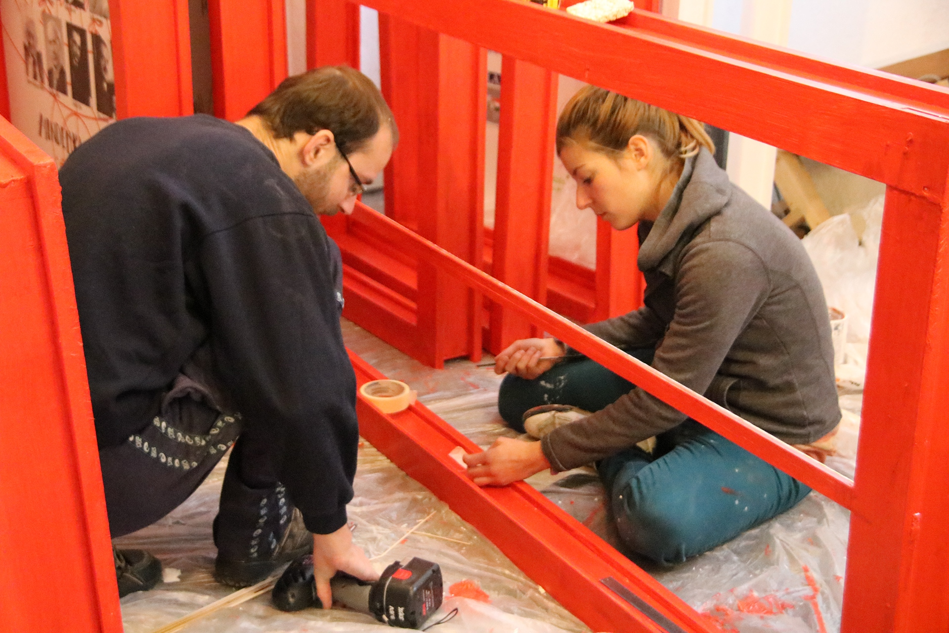 people painting a door frame with red cover paint
